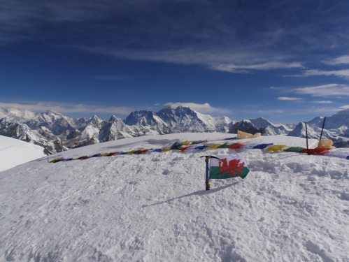 Flags on the summit of Mera Peak with a view of Everest in the background