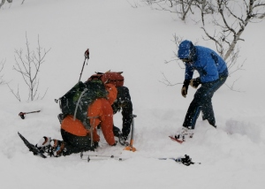 students in Norway using a transceiver to pinpoint a buried casualty